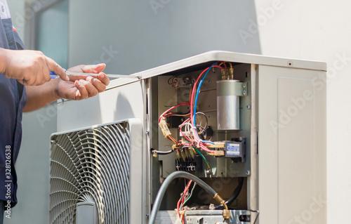 Carta da parati Male technician hands using a screwdriver fixing modern air conditioner, repairi