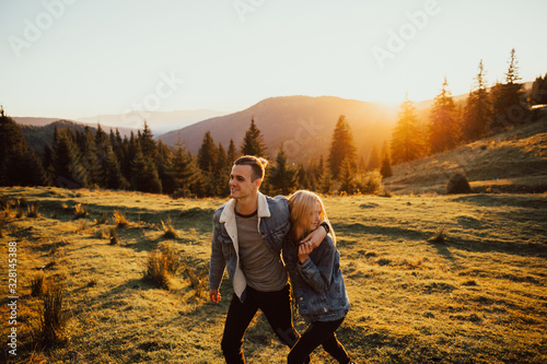 Man and woman walking on the mountain at sunset фототапет