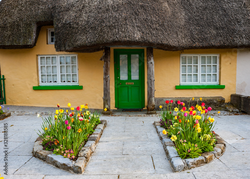 Obraz na plátne Colourful flowerbeds outside old traditional Irish cottage in rural Ireland