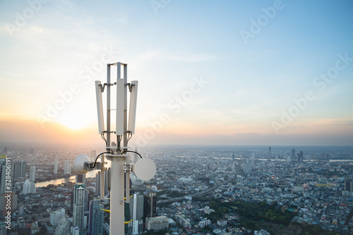 Fotografering Telecommunication tower with 5G cellular network antenna on city background