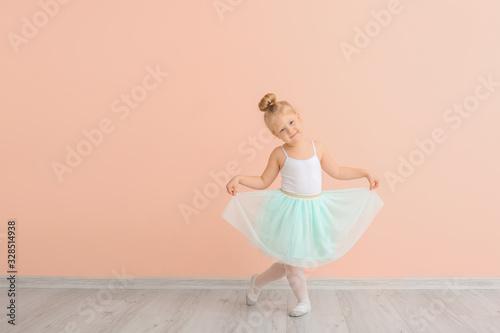 Photo Cute little ballerina near color wall