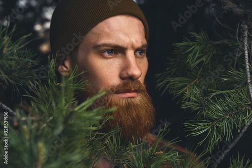 Fototapeta Portrait brutal bearded hipster man in the forest