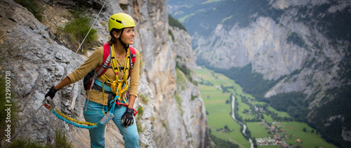 Obraz na plátně Pretty, female climber on a via ferrata - climbing on a rock in Swiss Alps