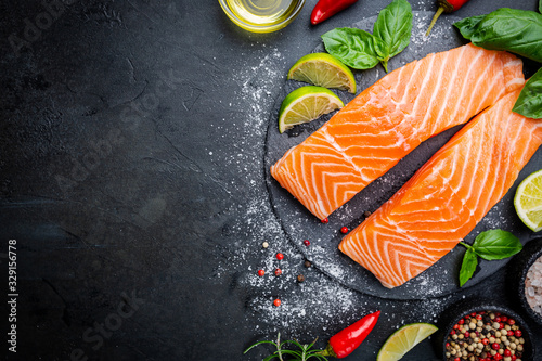 Fotografia Raw salmon fillet and ingredients for cooking, seasonings and herbs on a dark background