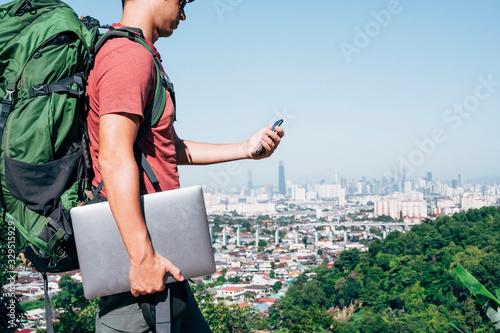 Fotografie, Obraz Digital nomad man traveling the world working with smartphone