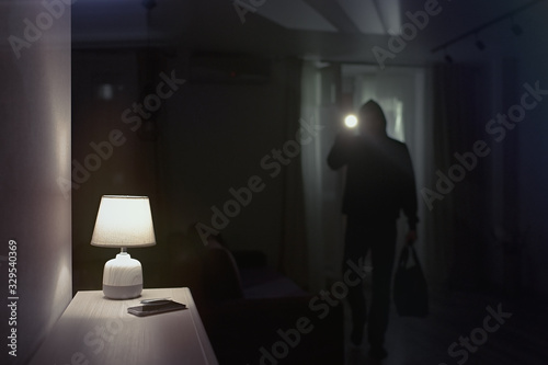 Photo Burglar inside of a house with flashlight