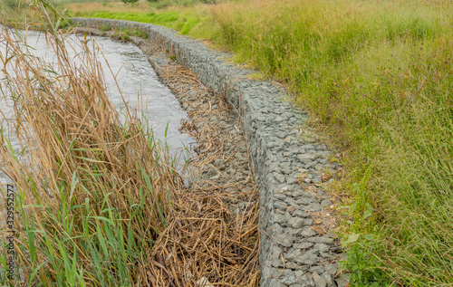 Gabion retaining walls to control erosion and flooding on the banks of a fast fl Poster Mural XXL