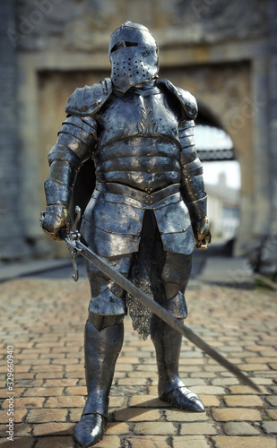 Fényképezés Powerful medieval knight standing with a full suit of armor and holding a sword weapon in front of his castle
