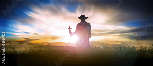 Photo priest on the hill at sunset with the cross