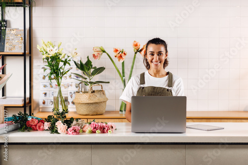 Tela Female florist in apron standing standing at ther counter and looking at camera