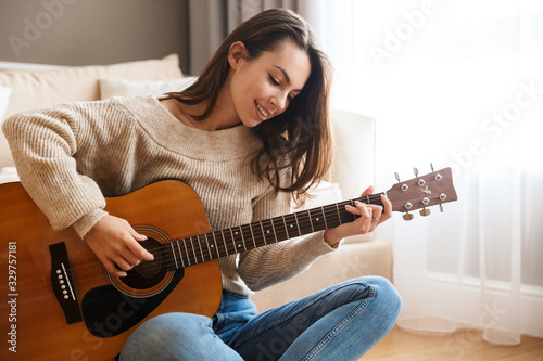 Fotografia Image of happy beautiful woman playing guitar and composing song