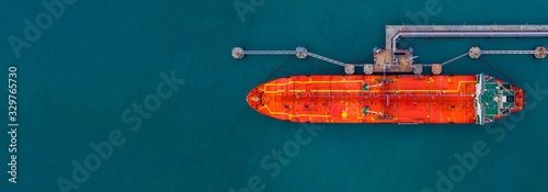 Photo Red cargo tanker ship vessel at port with marine loading arms, Global business oversea commercial trade logistic import export oil and gas petrochemical refinery industry transport worldwide