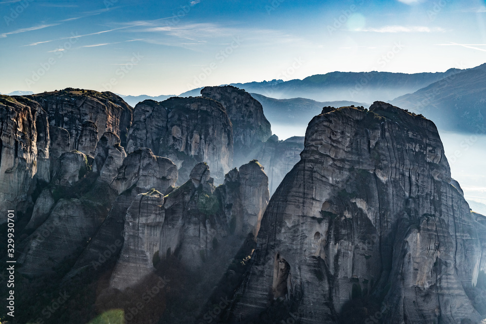 Aerial view of Unesco monument Meteora, the mountains, the landmark of Greek, sunny weather, fog, haze over a valley