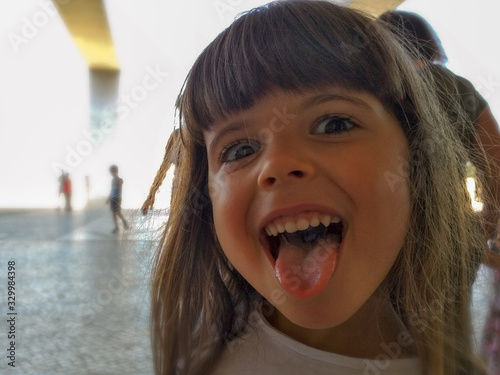 Photo Portrait Of Cute Girl Sticking Out Tongue