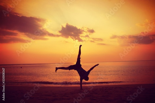 Fotografiet Silhouette Man Doing Handstand On Beach At Sunset