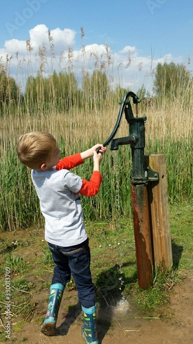 Fotografia Boy Fetching Water Using Hand Pump