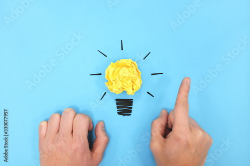 Yellow light bulb flat lay with human hands in blue background. Creativity and new business ideas concept.