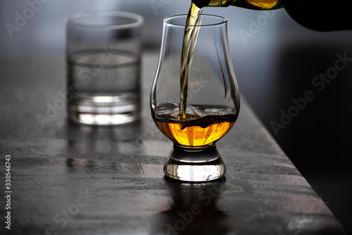 Canvas Print Pouring in tulip-shaped tasting glass Scotch single malt or blended whisky