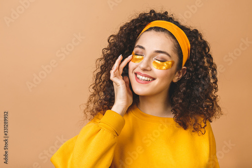 Slika na platnu Image of young pure beautiful curly woman isolated over beige background take care of her skin with under eye patches