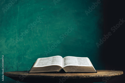 Tablou Canvas Open Holy Bible on a old round wooden table
