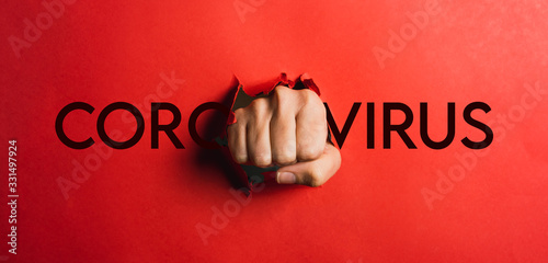 Foto Human hand tearing red paper with the word coronavirus, concept in the fight aga