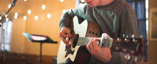 Fotografie, Obraz Young man playing on acoustic guitar