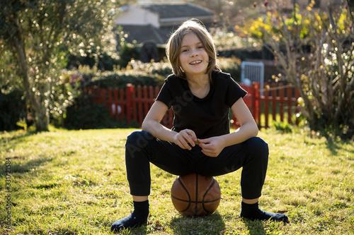 Fotografia, Obraz Bambino felice seduto in giardino su un pallone da basket senza calzini