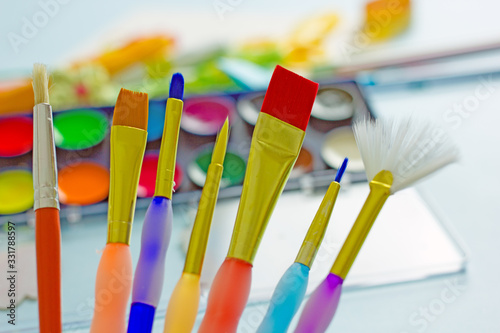 Tela Multi-colored brushes for painting on a background of watercolor paints
