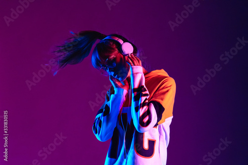 Stylish fashion teenager model wearing hoodie and headphones listening dj music dancing in purple neon lights. Young teen girl enjoy cool music 90s party mix in violet studio background. Copy space.