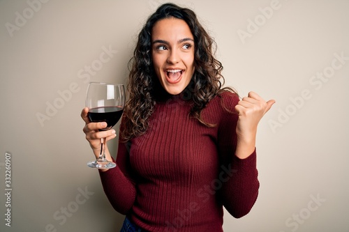 Tablou Canvas Young beautiful woman with curly hair drinking glass of red wine over white back