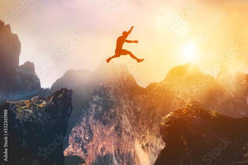 Fotografia Man jumping between rocks. Overcome a problem for a better future