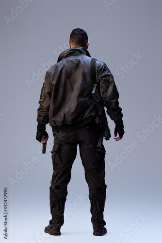 Photo back view of cyberpunk player holding gun and standing on grey
