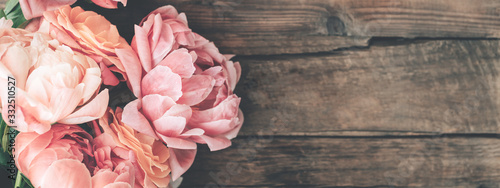 Fotografia Fresh bunch of pink peonies and roses on wooden rustic background
