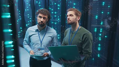 Fotografia Team of professional data center engineers setting server hardware working on laptop coworking in digital server room