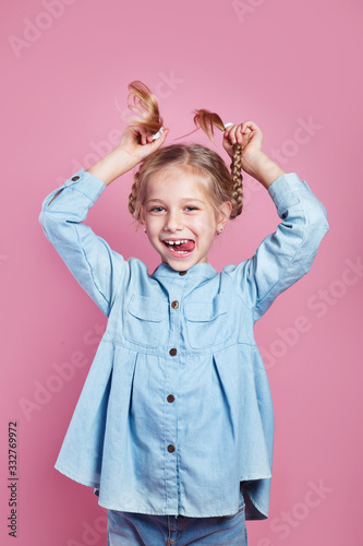 Fotografia Funny little girl holding her pigtails and sticking tongue