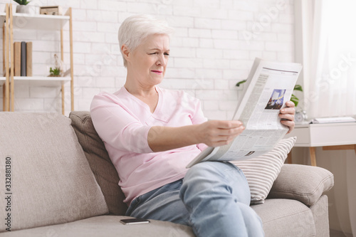 Senior lady squinting and holding newspaper far from eyes