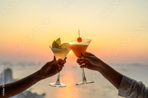Tableau sur Toile Couple enjoying of Cheers glass of cocktail in a restaurant  at sunset view sea