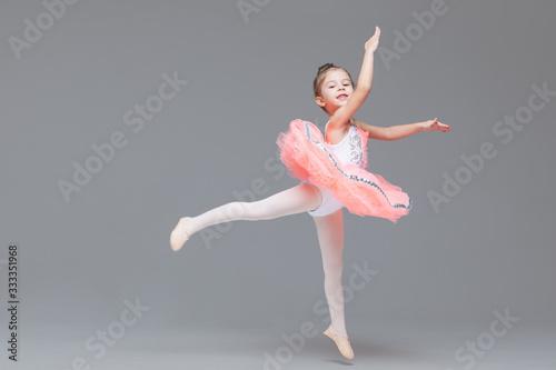 Fotografiet Cute adorable ballerina little girl in pink tutu dance practices ballet dancing