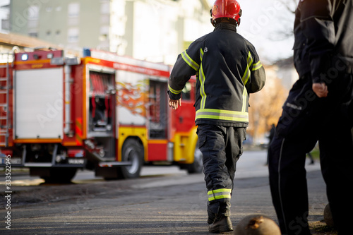 Fotografia, Obraz Fireman in uniform in front of fire truck going to rescue and protect