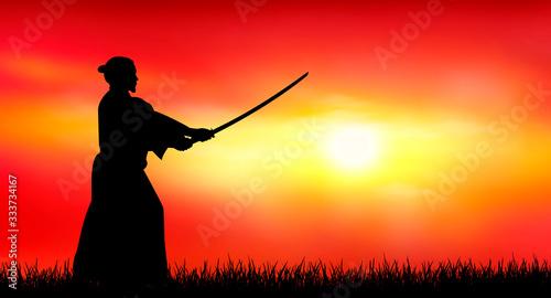 Fotografia Japanese warrior samurai with a sword at sunset