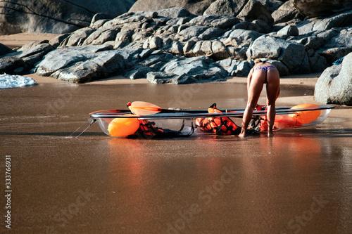 Active leisure, girl with canoe on the shore of a seaside resort Fototapeta
