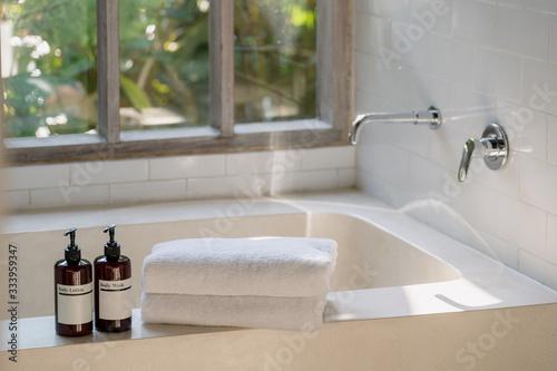 Two bottle of body wash lotion and shower gel on top of white ceramic bathtub Fototapeta