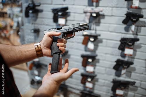 Obraz na płótnie Man choosing new handgun in gun shop