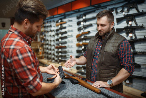 Canvas Print Man with owner choosing handgun in gun shop