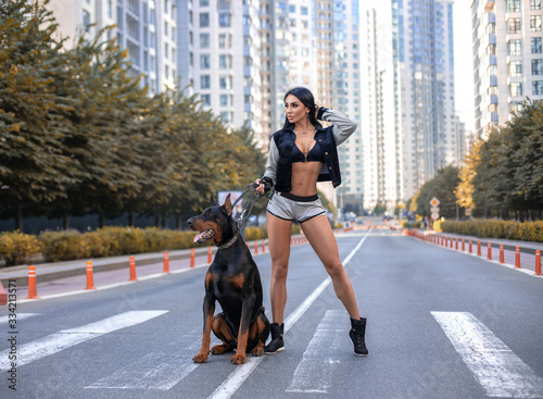 Leinwand Poster Fitness girl walking with huge Doberman dog