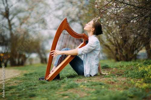 Photo Woman harpist sits on grass and plays harp among blooming apricot trees