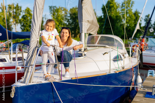 Stampa su Tela Portrait of smiling mother and daughter on prow of sailboat or yacht anchored in marina at bright sunny day