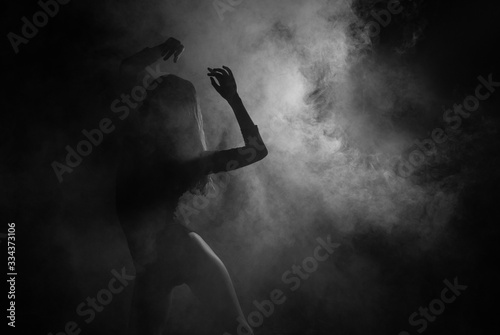 Valokuva Female silhouette dancing in shadow and smoke