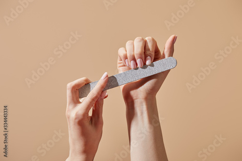 Fotografiet Partial view of woman filing fingernails with emery board isolated on beige