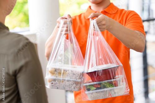 Fototapeta Delivery man in orange uniform delivering Asian food boxes in plastic bags to a